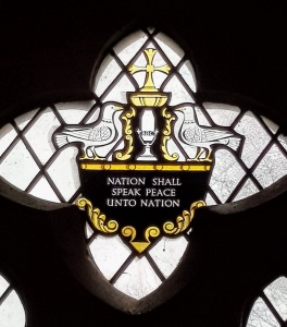 Stained glass window featuring a BBC microphone, doves of peace and the caption Nation Shall Speak Peace Unto Nation